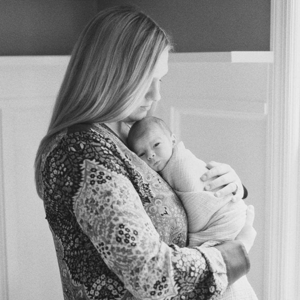 mom-holds-newborn-against-her-chest-while-newborn-looks-at-camera