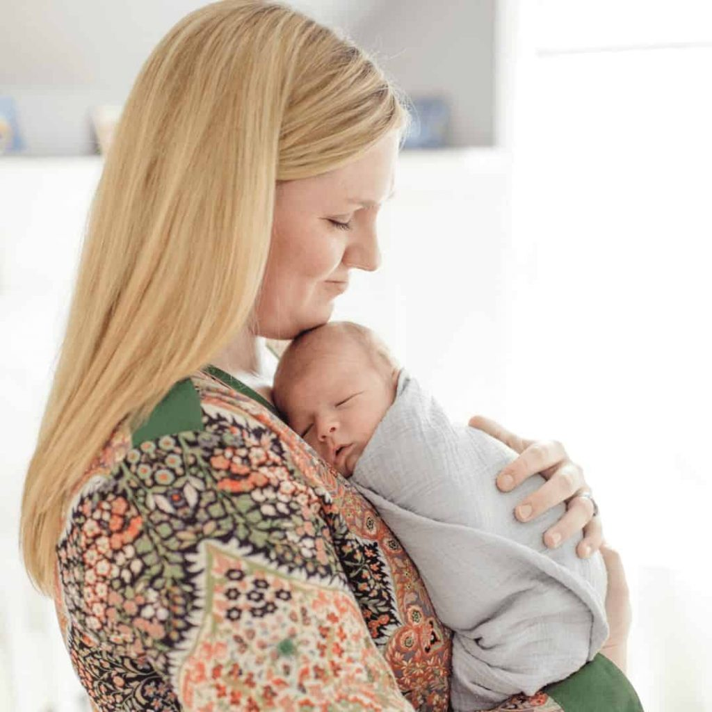 new-mom-holding-infant-against-her-chest-with-slight-smile-on-her-face