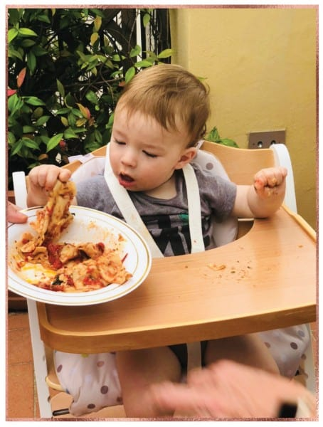 Baby eating homemade pasta in Italy