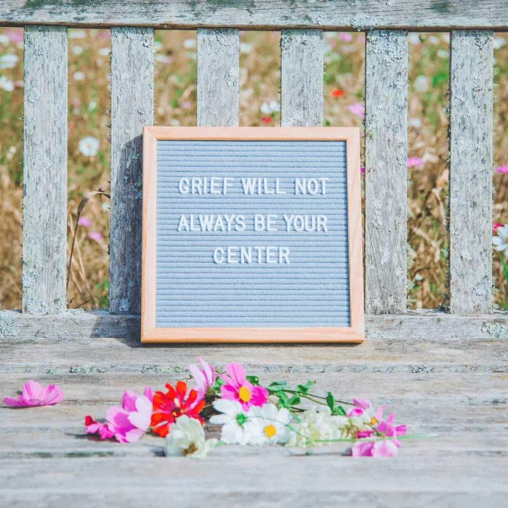gray-letterboard-propped-on-gray-bench-with-colorful-flowers-in-front-of-it-the-letterboard-says-grief-will-not-always-be-your-center