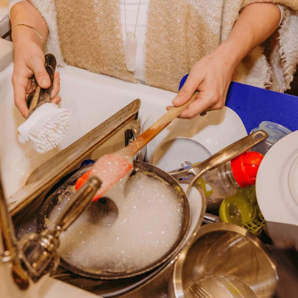 womans-hands-holding-spatula-and-dish-brush-over-sink-full-of-dishes-she-is-washing