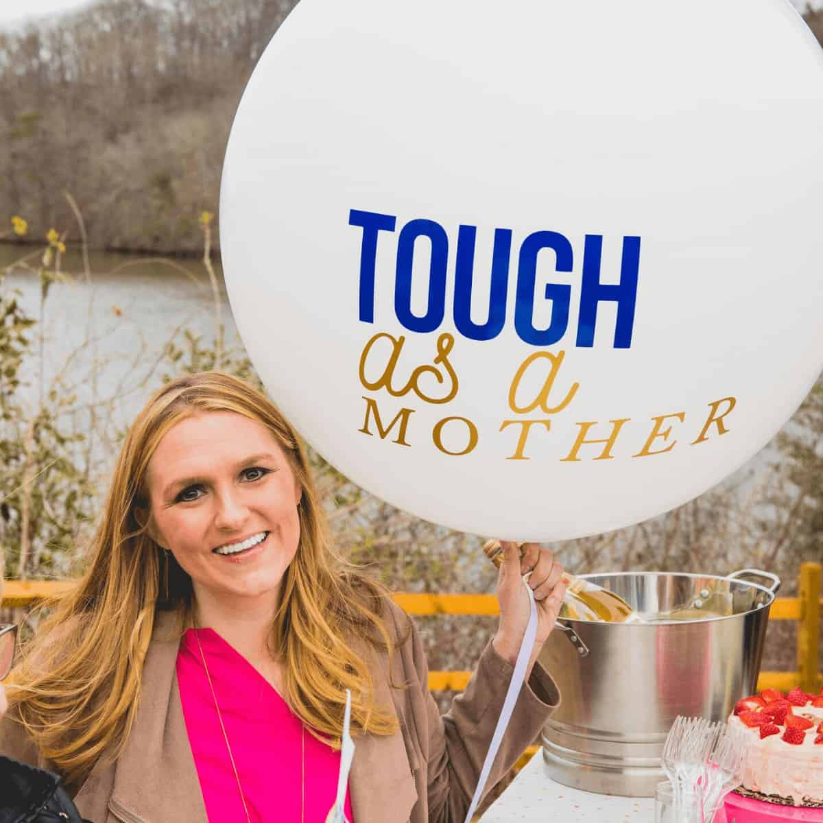 blonde-woman-in-pink-shirt-and-brown-jacket-smiling-holding-balloon-that-has-tough-as-a-mother-written-on-it