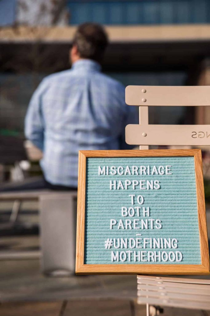 Letterboard about Miscarriage with Grieving Dad in Background