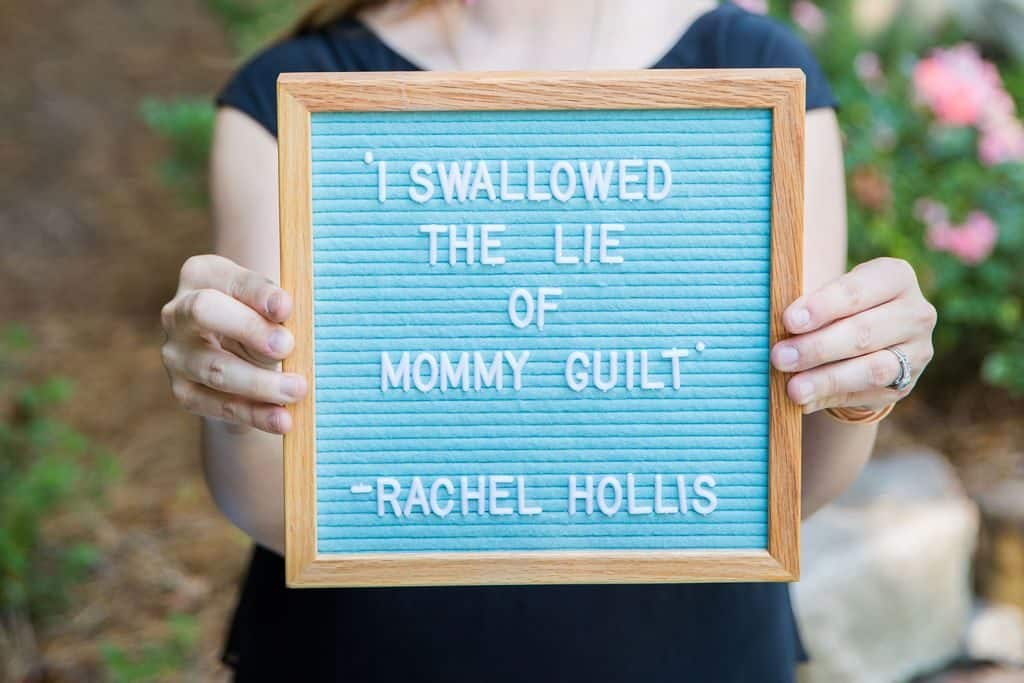 hands holding letterboard with a rachel hollis quote that says I swallowed the lie of mom guilt