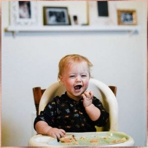 Laughing baby sitting in high chair while eating baby food