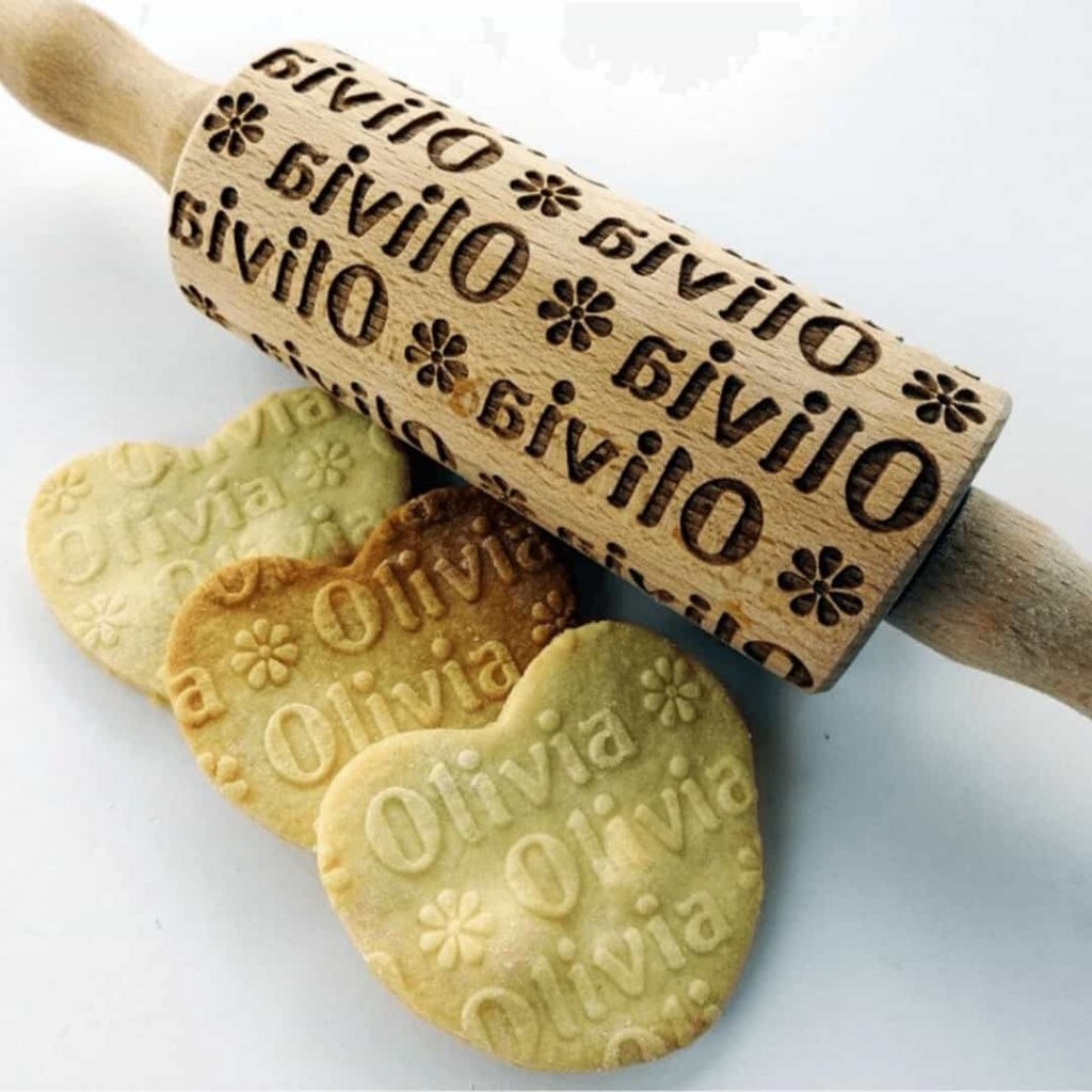 personalized-rolling-pin-that-says-olivia-with-heart-shaped-cookies-with-olivia-rolled-into-them