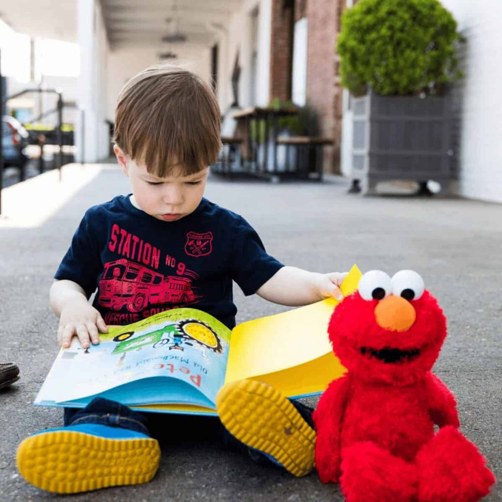 2-year-old-boy-reading-pete-the-cat-old-macdonald-book-with-elmo-sitting-at-his-feet