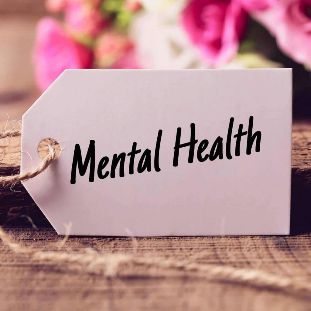 a tag that says mental health sitting in front of blurred flowers on a wooden table