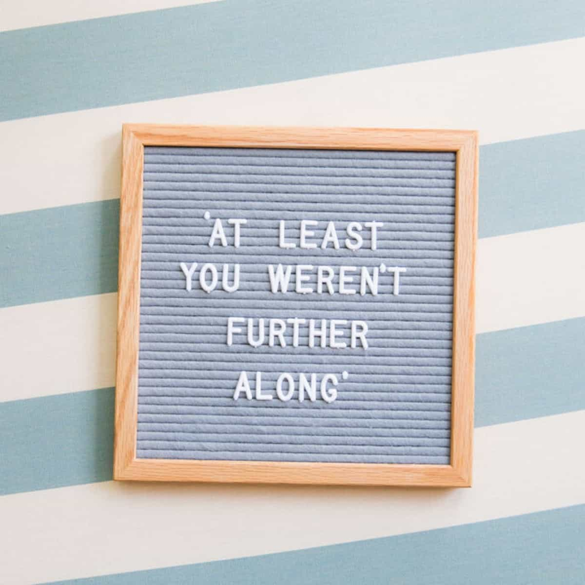 letterboard-on-blue-and-white-background-that-says-at-least-you-werent-further-along