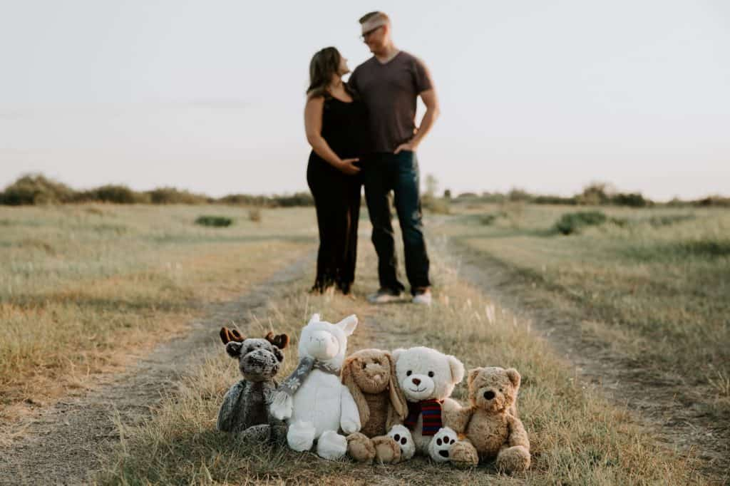 rainbow baby maternity shoot wit teddy bears representing 5 miscarriages
