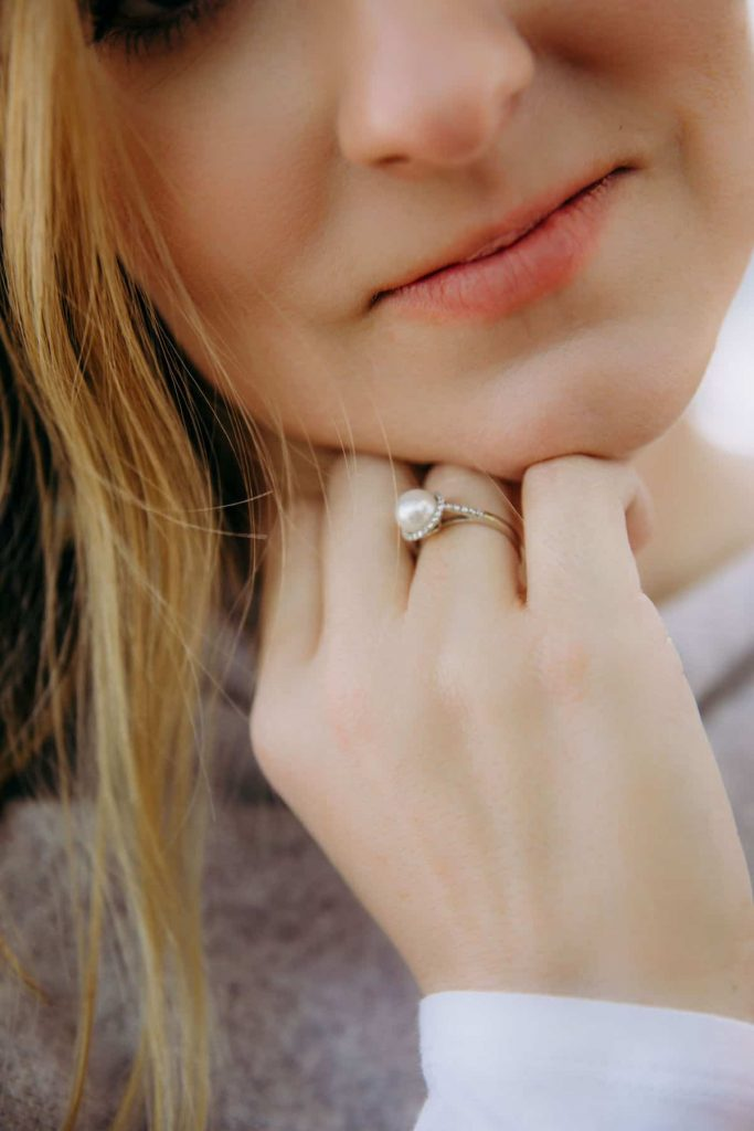 woman-with-hand-to-face-showing-pearl-ring-that-is-a-symbol-of-children-lost-to-miscarriage