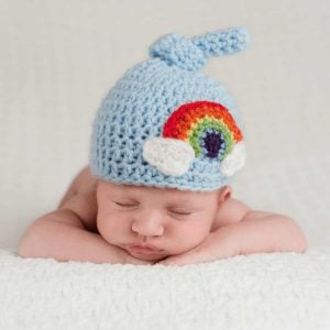 Infant baby is wearing a crochet hat that includes a rainbow design