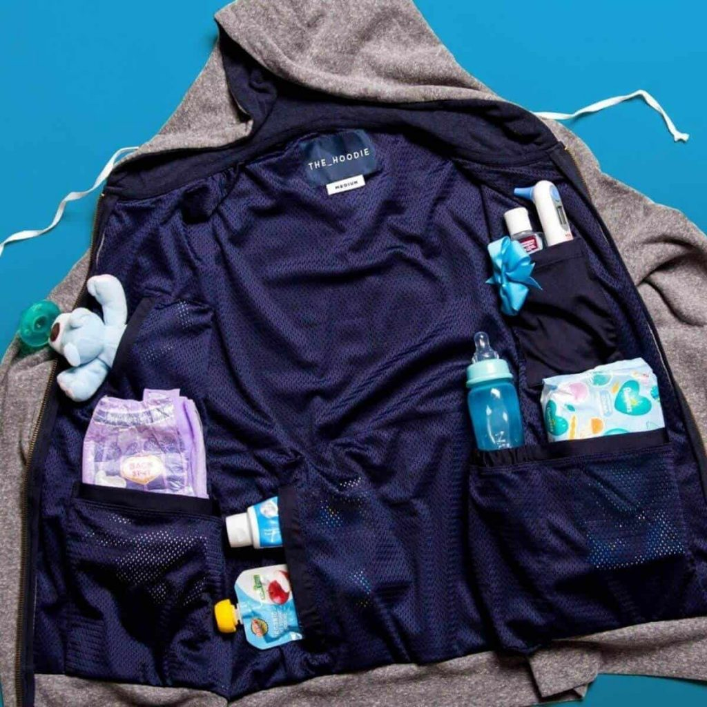 diaper-bag-alternative-the-dad-hoodie-lies-open-on-a-blue-background-with-the-interior-of-the-hoodie-showing-pockets-holding-items-like-wipes-diapers-and-a-kids-cup