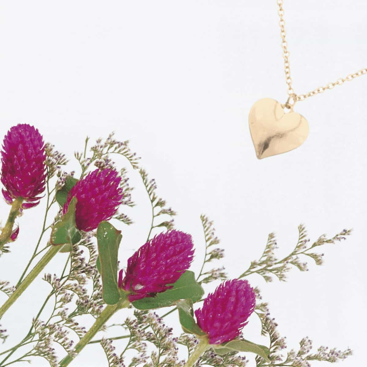 flat-lay-photo-of-pinkish-purple-flowers-in-the-bottom-left-corner-and-a-golden-heart-shaped-necklace-in-the-upper-right-corner-meant-to-show-2-healing-gifts-for-miscarriage