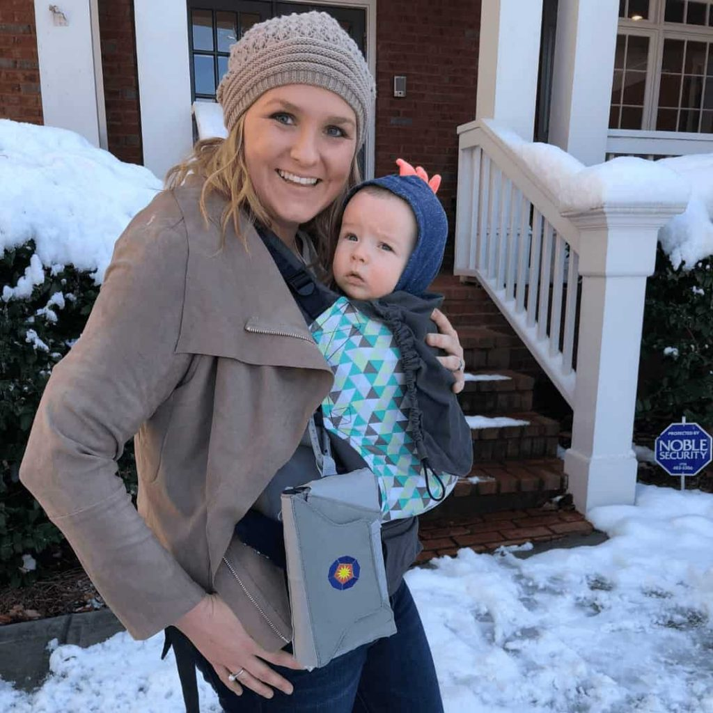 mom-standing-in-snow-wearing-baby-in-tula-carrier-with-bratpack-diaper-bag-alternative-strapped-to-tula