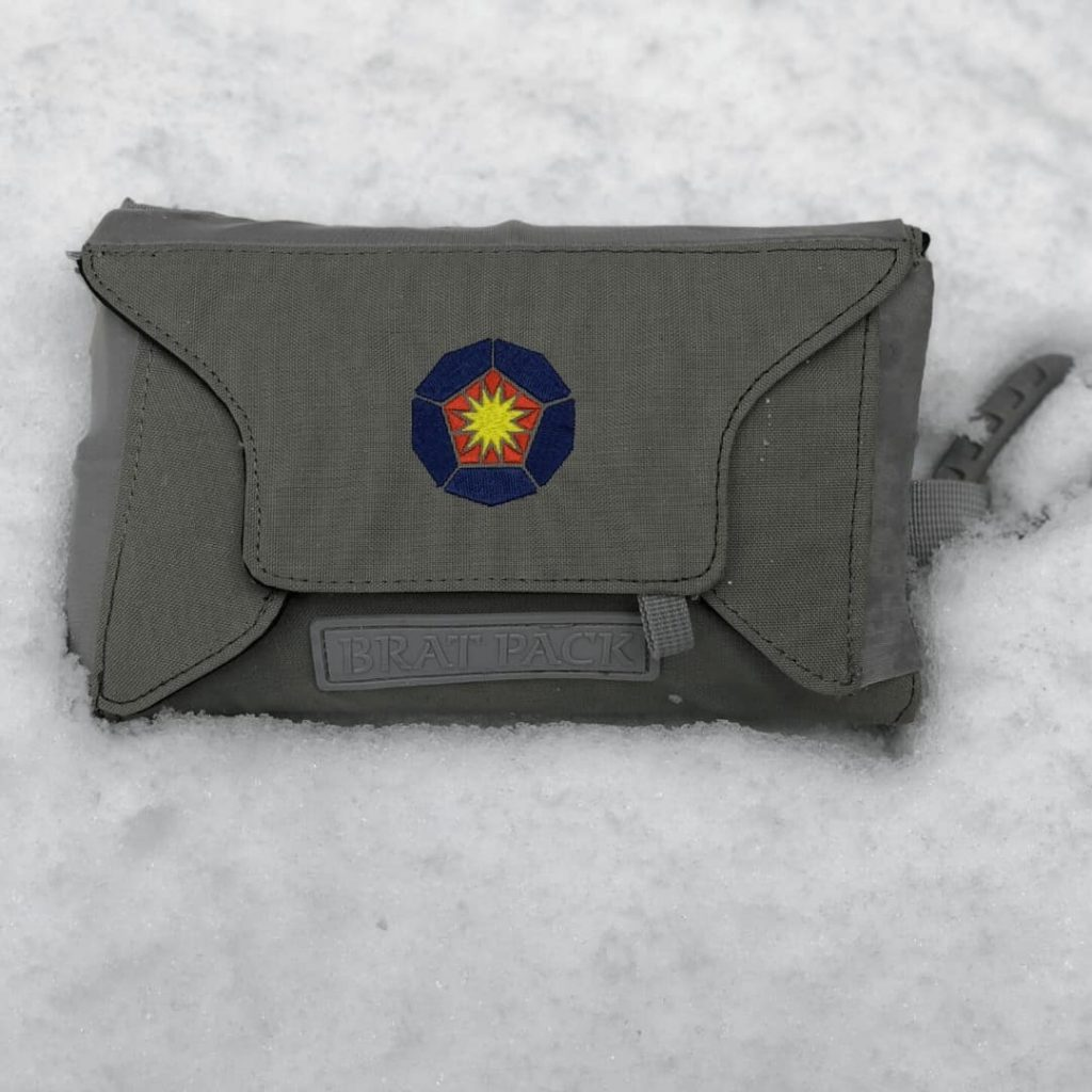hand-held-diaper-bag-alternative-called-bratpack-lying-in-snow-showing-from-of-bag