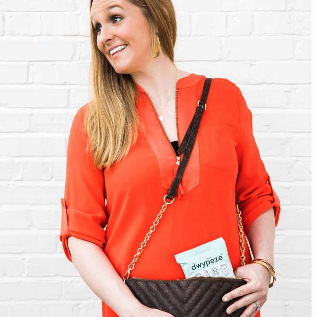 woman-in-red-dress-holding-purse-with-pocket-sized-diaper-bag-alternative-called-dwpypeze-sticking-out-of-top