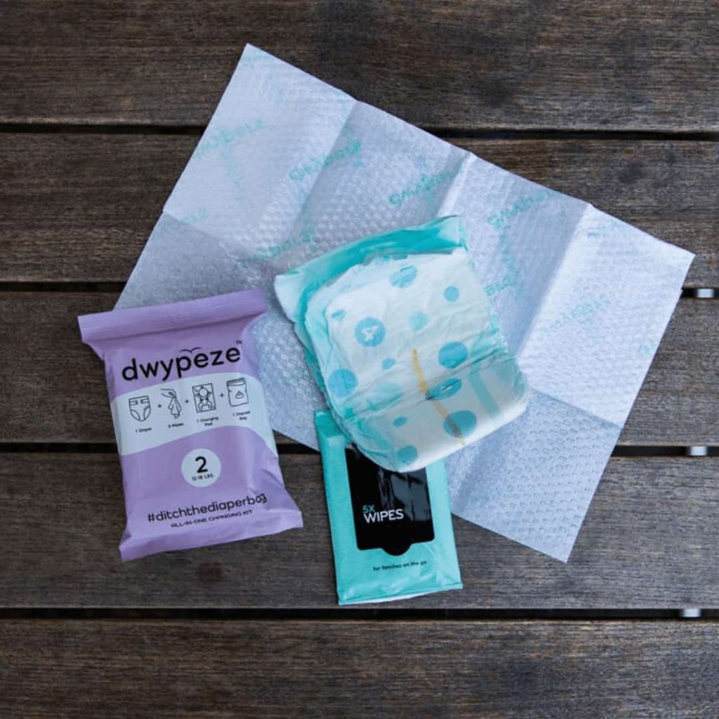 contents-of-diaper-bag-alternative-dwypeze-laid-out-on-able-including-diaper-wipes-and-changing-pad