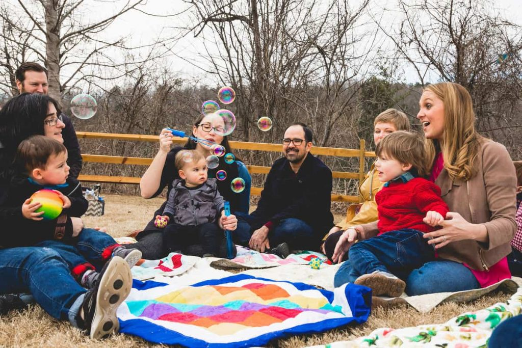 men-women-and-children-sitting-around-rainbow-baby-quilt-blowing-bubbles-and-smiling