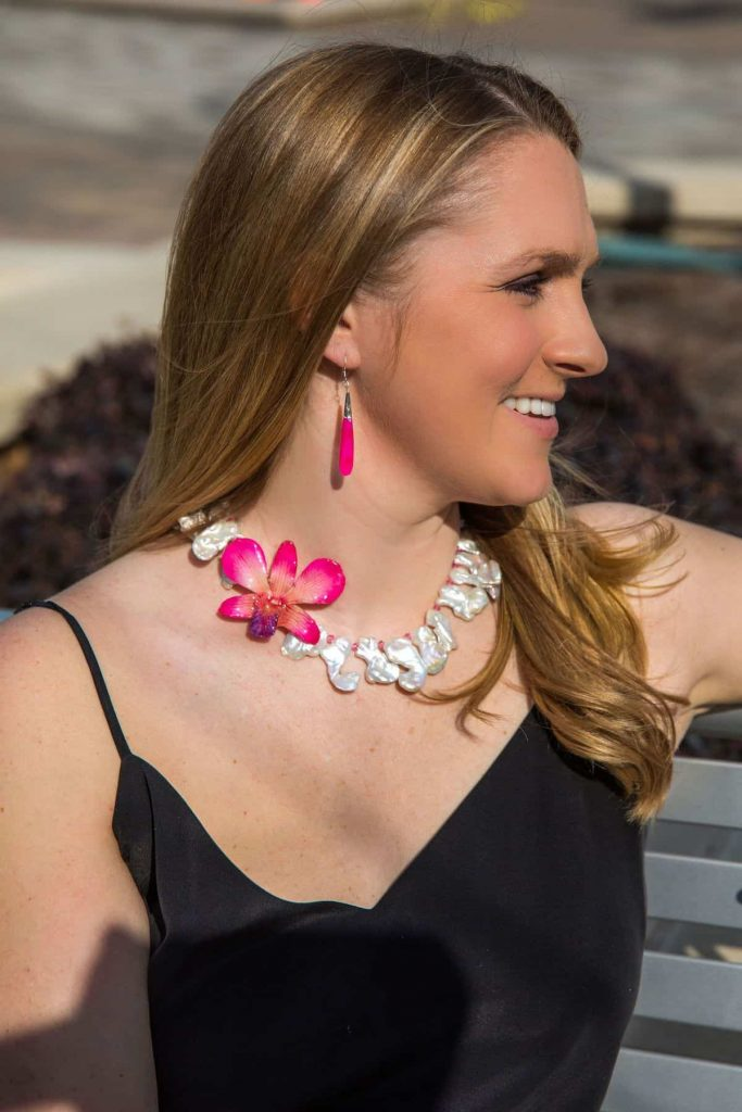 woman-smiling-wearing-preserved-orchid-necklace-and-pink-crystal-earrings
