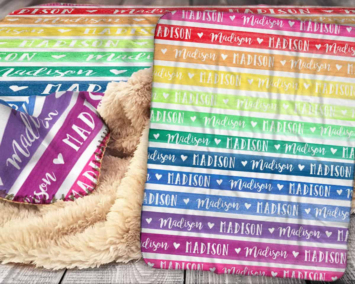 fuzzy-blanket-that-has-fuzz-on-one-side-and-straight-lines-on-the-other-side-that-make-a-rainbow-with-their-colors-this-blanket-is-customized-with-the-name-madison-fully-customizable-it-makes-a-great-rainbow-baby-gift