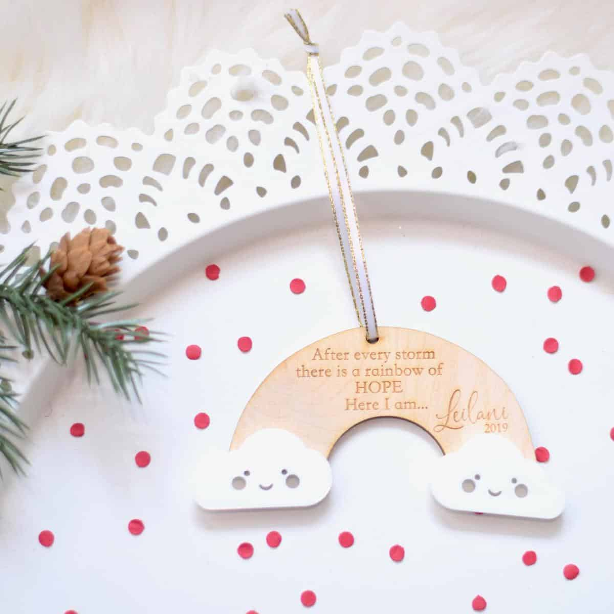 rainbow-shaped-wooden-christmas-ornament-in-original-wood-color-with-clouds-on-each-end-of-the-rainbow-sitting-on-top-of-a-white-tray-with-red-polka-dots-with-a-sprig-of-pine-and-a-small-pine-cone-resting-on-the-side-of-the-plate-the-wooden-ornament-says-after-every-storm-there-is-a-rainbow-of-hope-here-I-am-and-is-customized-with-babys-name-and-the-year