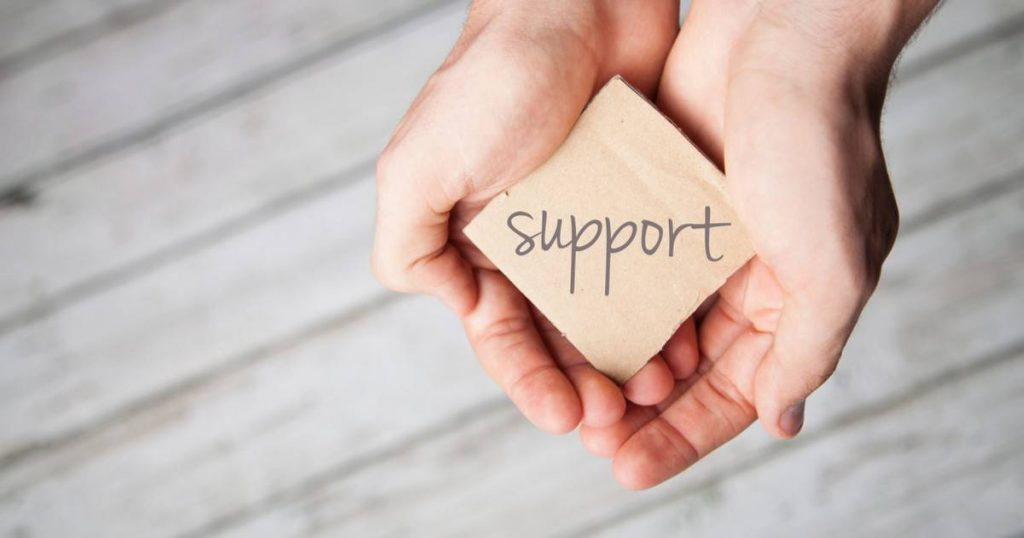 womans-hands-holding-wooden-ornament-that-says-support