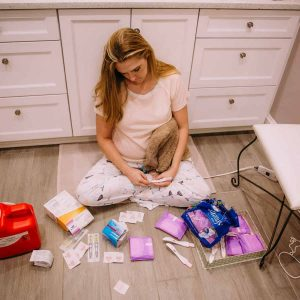 woman-on-floor-mourning-miscarriage-with-various-supplies-around-her