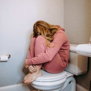 woman-in-red-sitting-on-closed-toilet-with-her-arms-wrapped-around-her-legs-and-her-head-buried