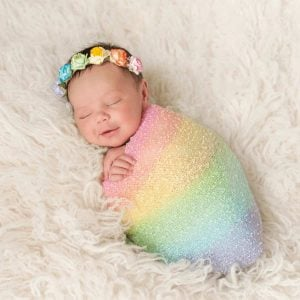 newborn-baby-with-dark-hair-and-rainbow-colored-flower-headband-lying-on-fuzzy-blanket-swaddled-in-rainbow-blanket