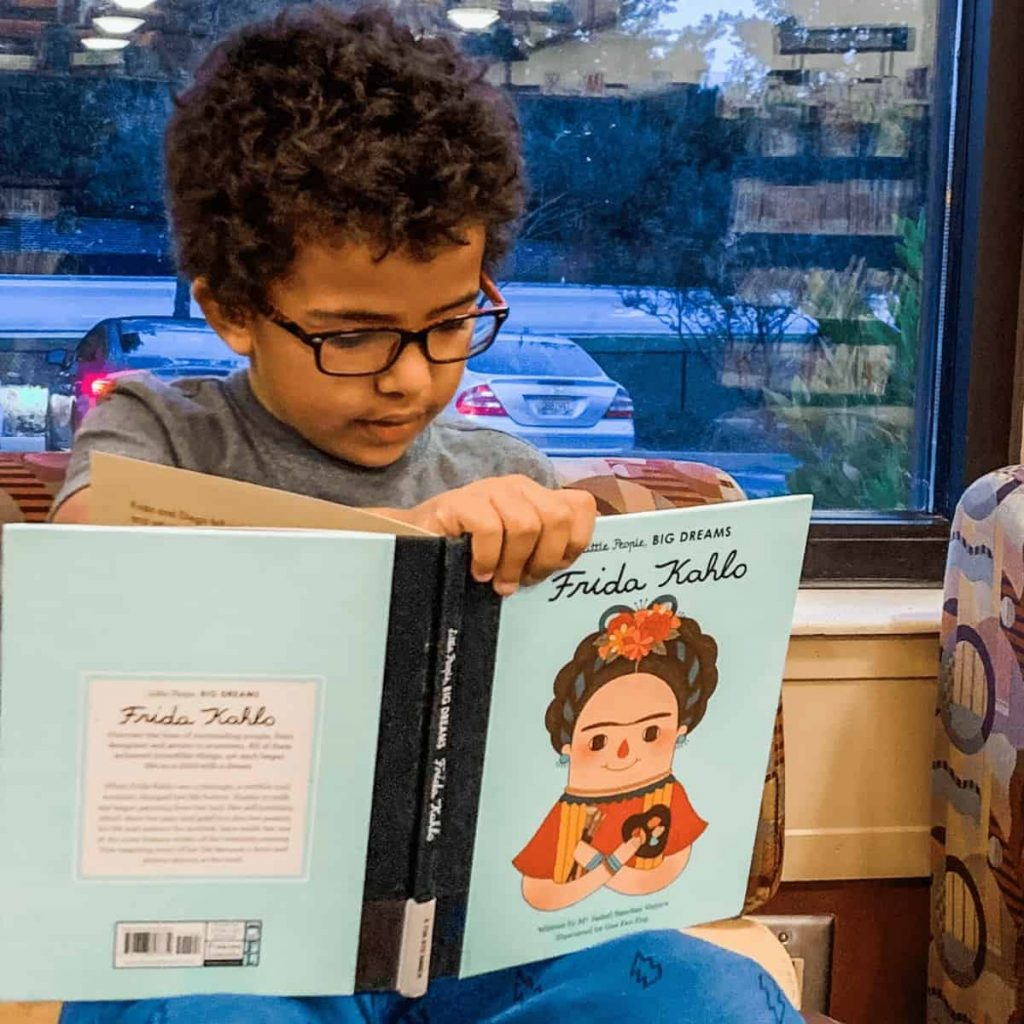 young-boy-sitting-in-front-of-window-reading-board-book-about-frida-kahlo