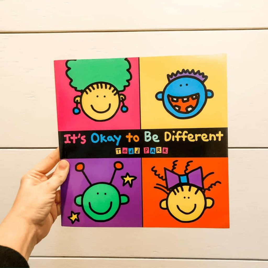 hand-holding-book-called-its-okay-to-be-different