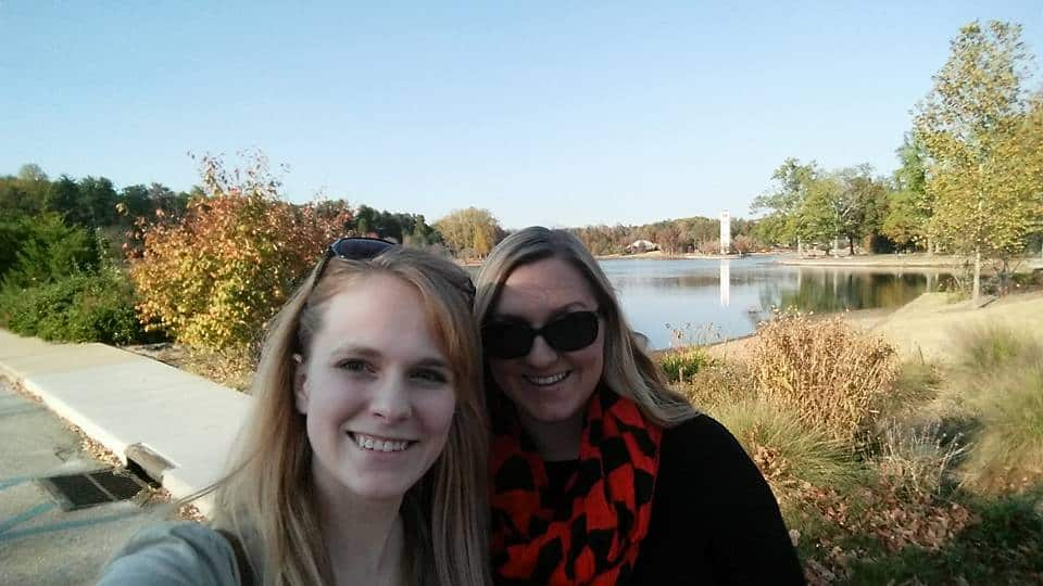 two-women-smiling-in-front-of-lake