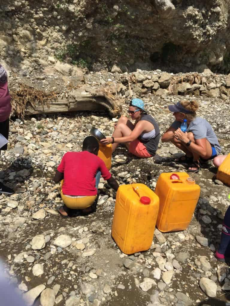 people-with-jugs-in-riverbed-in-haiti