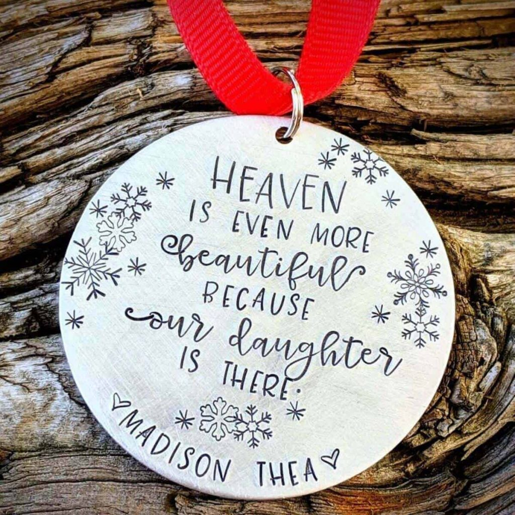 round silver miscarriage ornament on red string with engraved words that say heaven is even more beautiful because our daughter is there