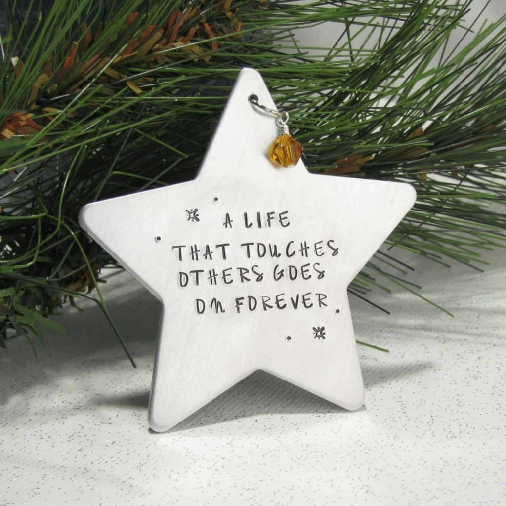 star-shaped-ornament-with-crystal-attached-sitting-in-front-of-pine-needles-that-says-a-life-that-touches-others-goes-on-forever