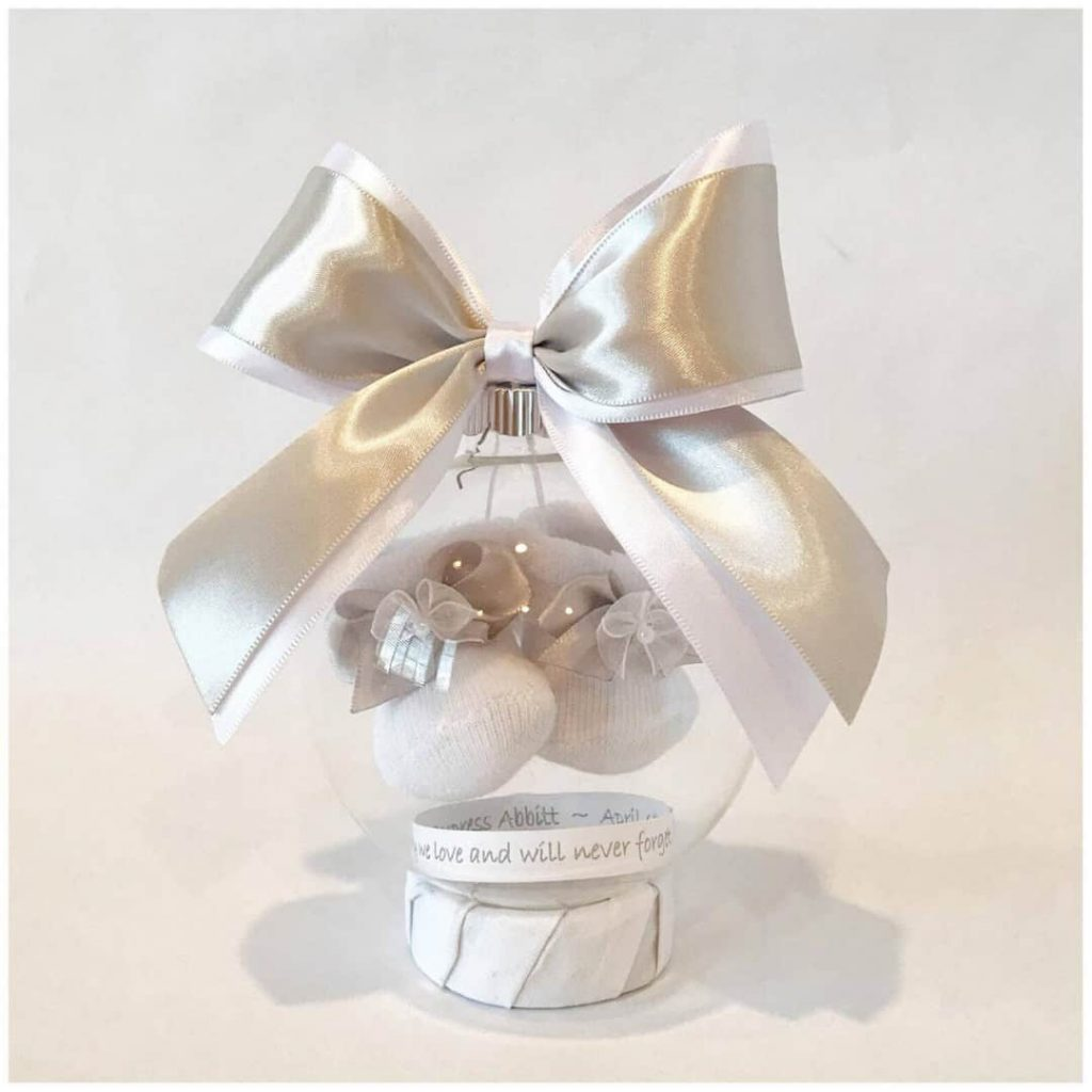 christmas-ornament-with-silver-ribbon-and-clear-ball-that-shows-baby-booties-inside-above-paper-with-memorial-writing