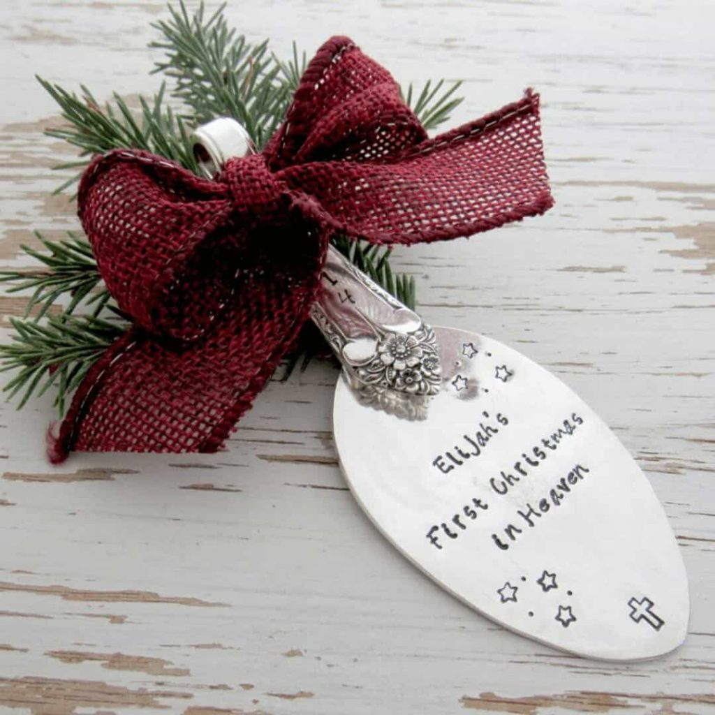 pine-needles-and-red-ribbon-hold-this-silver-ornament-that-says-first-christmas-in-heaven