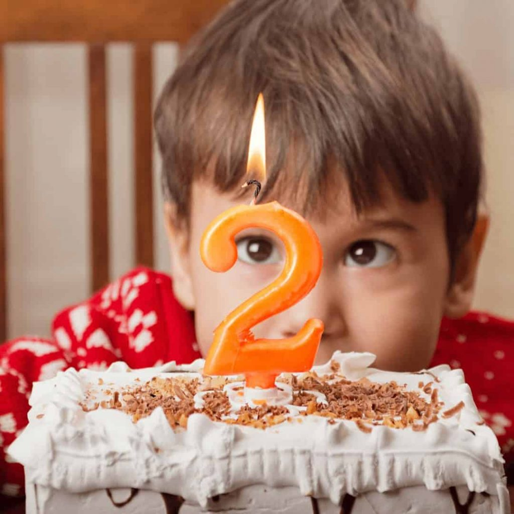 2-year-old-boy-crouching-behind-birthday-cake-with-a-lit-number-2-candle
