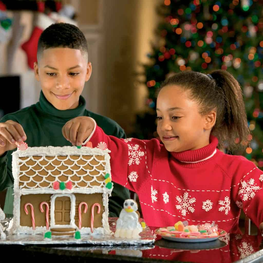 Kids decorating a gingerbread house