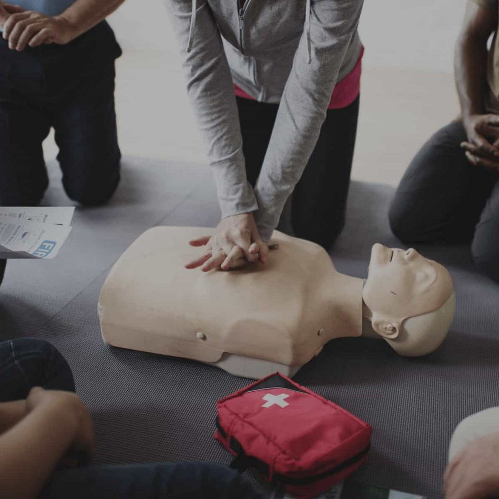 people-in-a-circle-in-a-first-aid-cpr-class-with-one-man-in-middle-practicing-chest-compressions-on-a-dummy