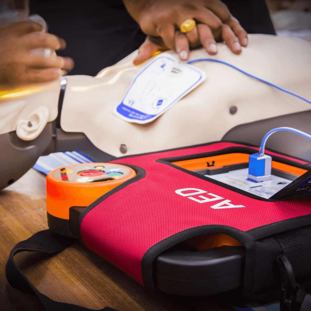 automatic-electronic-defibrillator-also-called-aed-being-placed-onto-dummy-in-cpr-first-aid-class