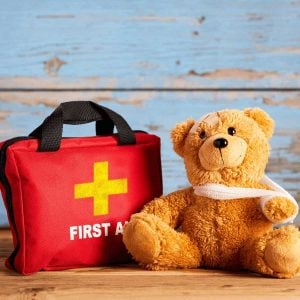 brown-teddy-bear-in-front-of-blue-wall-sitting-next-to-first-aid-kit