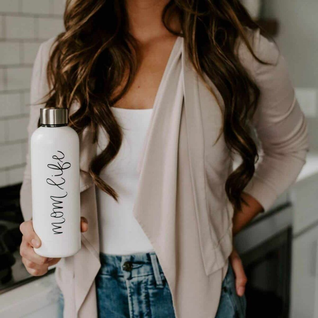 woman with long brown hair holding white water bottle that says mom life