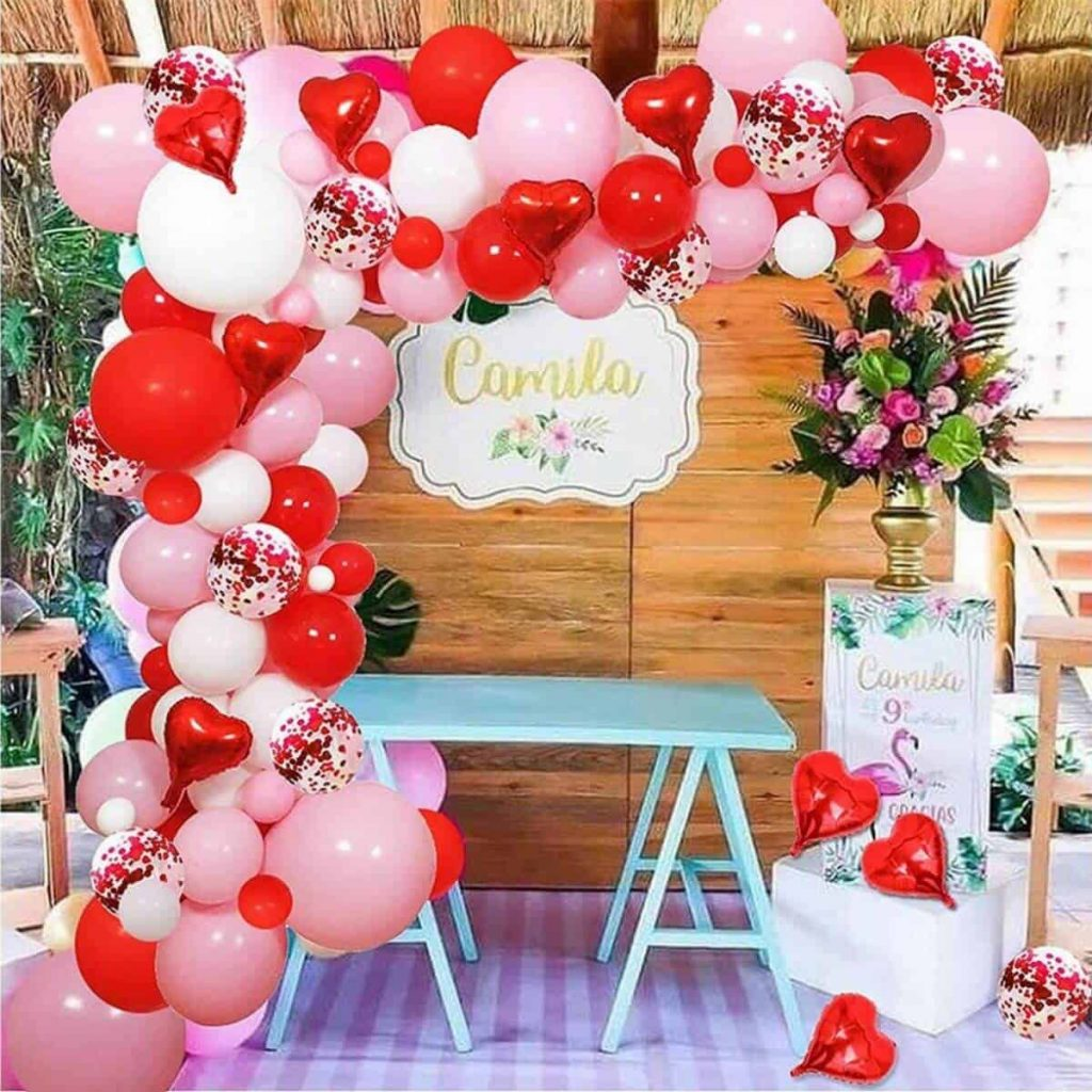 Gorgeous red, white, and pink balloon garland with valentines hearts in front of a wooden background