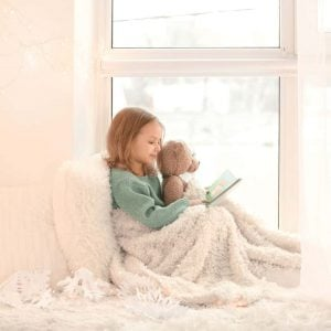 little-girl-sitting-in-window-seat-snuggled-in-winter-blankets-holding-teddy-bear-reading-a-book