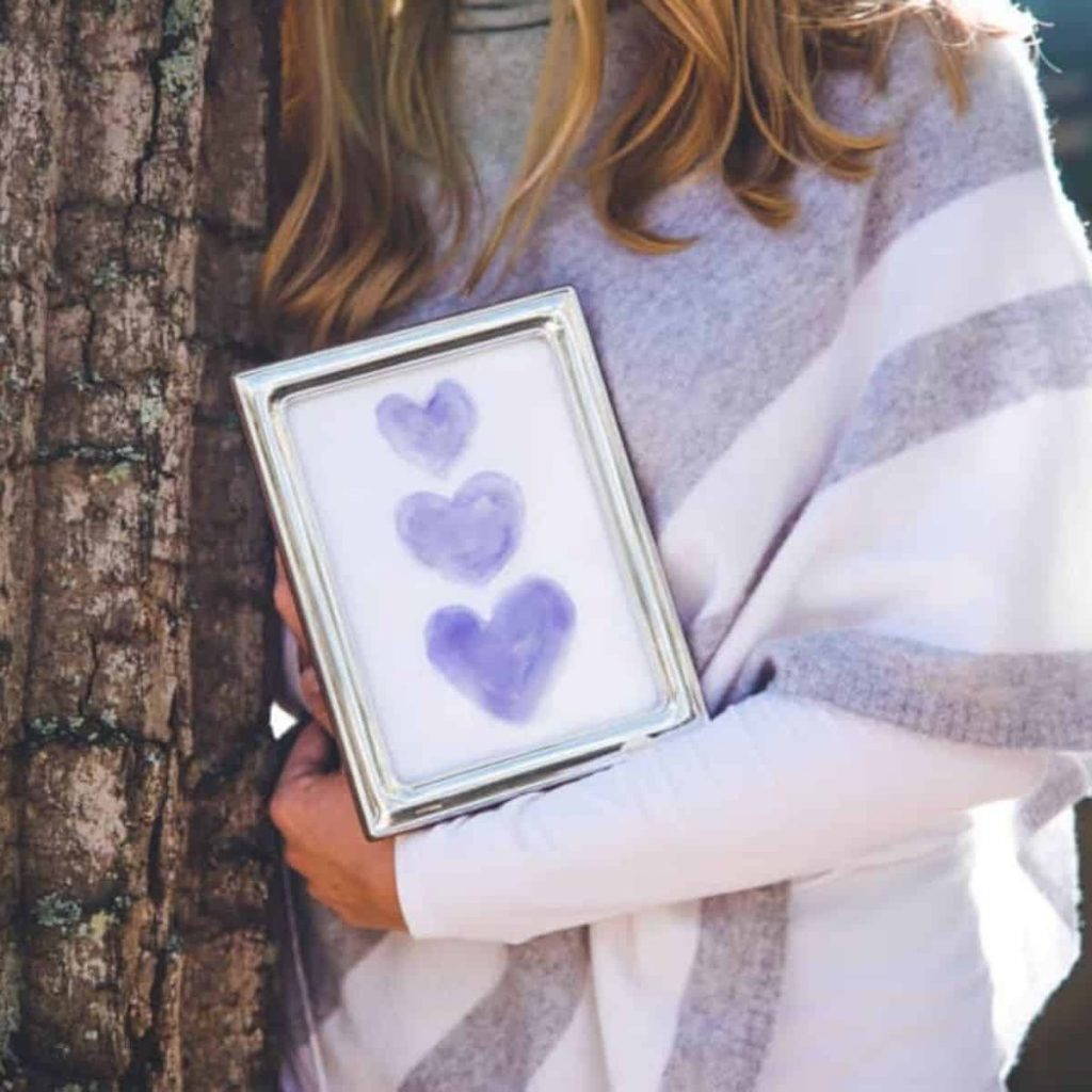 As part of a miscarriage care package, Tessa sent me artwork of 3 purple hearts to represent 3 losses. Here, I'm holding the artwork posing by a tree.