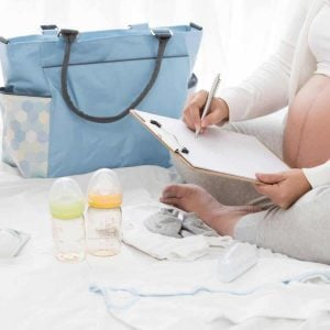 pregnant woman sitting on bed with baby items holding a note pad making a list of new baby must haves for her baby registry