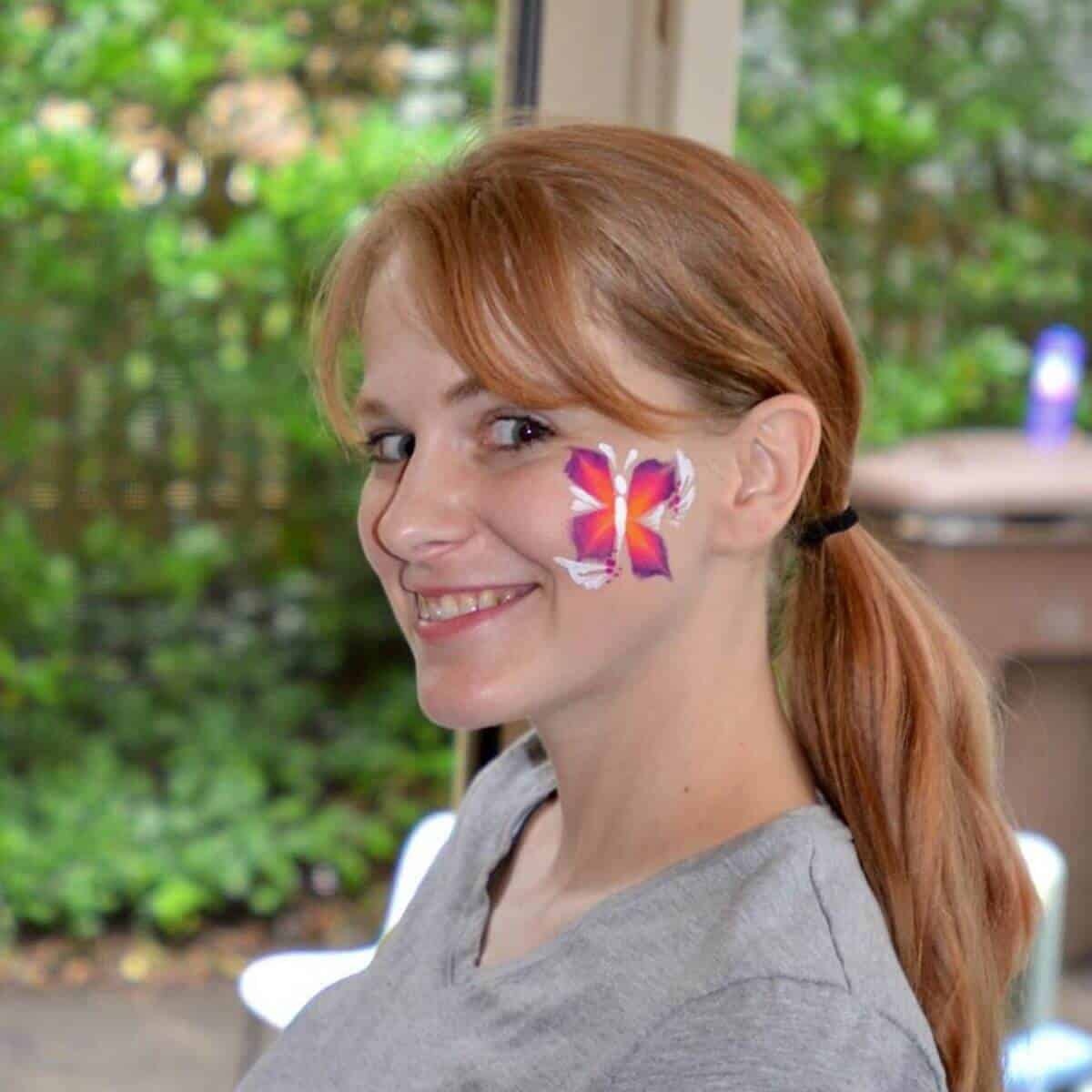 woman-smiling-at-camera-with-butterfly-on-her-face