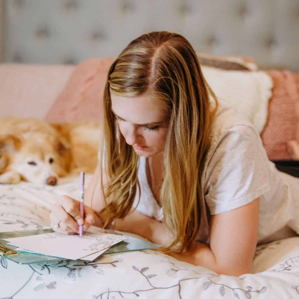 Woman laying in bed with her dog nearby as she journals about her experiences